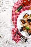 炒米用海鲜淡菜、虾和蓬蒿在一块板材有酒瓶、葡萄酒杯、毛巾和拔塞螺旋的在崩裂的白色 免版税库存图片