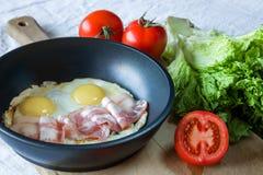 炒蛋和烟肉在煎锅在桌特写镜头 免版税库存图片