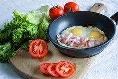 炒蛋和烟肉在煎锅在桌特写镜头 库存图片