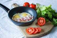 炒蛋和烟肉在煎锅在桌特写镜头 免版税库存照片
