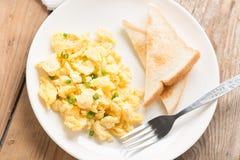 炒蛋和面包在白色板材 顶视图 免版税库存图片