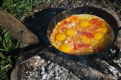 炒蛋在平底锅的煤炭油煎了开火,烹调在开火 免版税库存图片