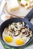 炒蛋用对煎锅、切的乳酪和草本的蘑菇 图库摄影