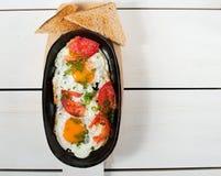 炒蛋用新鲜的蕃茄和新鲜的草本在平底锅油煎了 服务用面包多士 免版税库存照片