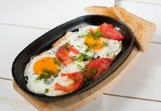 炒蛋用新鲜的蕃茄和新鲜的草本在平底锅油煎了 服务用面包多士 库存照片