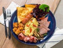 炒蛋用油煎的烟肉,火腿,油煎了香肠、油炸物、蘑菇、蕃茄和多士 免版税库存照片