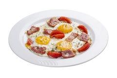 炒蛋用火腿和蕃茄在一块白色板材 免版税库存图片