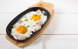 炒蛋用烟肉和新鲜的草本在平底锅油煎了 服务用面包多士 免版税图库摄影