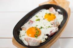 炒蛋用烟肉和新鲜的草本在平底锅油煎了 服务用面包多士 免版税库存图片