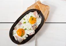 炒蛋用烟肉和新鲜的草本在平底锅油煎了 服务用面包多士 图库摄影