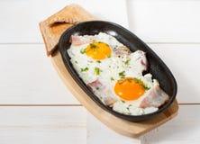 炒蛋用烟肉和新鲜的草本在平底锅油煎了 服务用面包多士 库存照片