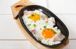 炒蛋用烟肉和新鲜的草本在平底锅油煎了 服务用面包多士 库存图片