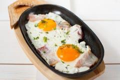 炒蛋用烟肉和新鲜的草本在平底锅油煎了 服务用面包多士 免版税库存照片