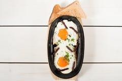 炒蛋用熏制的香肠和新鲜的草本在平底锅油煎了 服务用面包多士 免版税库存照片