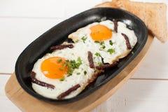 炒蛋用熏制的香肠和新鲜的草本在平底锅油煎了 服务用面包多士 免版税库存图片