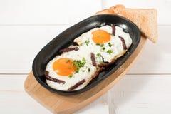炒蛋用熏制的香肠和新鲜的草本在平底锅油煎了 服务用面包多士 图库摄影