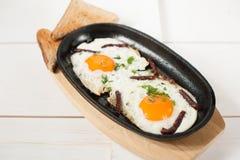 炒蛋用熏制的香肠和新鲜的草本在平底锅油煎了 服务用面包多士 库存照片