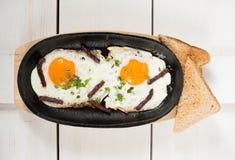 炒蛋用熏制的香肠和新鲜的草本在平底锅油煎了 服务用面包多士 免版税图库摄影