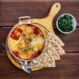 炒蛋用蕃茄、乳酪和香料在铝煎锅有把柄的有自创稀薄的lavash和水多的绿色的 免版税库存照片