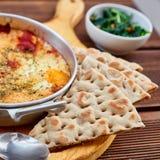 炒蛋用蕃茄、乳酪和香料在铝煎锅有把柄的有自创稀薄的lavash和水多的绿色的 库存图片