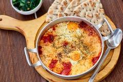 炒蛋用蕃茄、乳酪和香料在铝煎锅有把柄的有自创稀薄的lavash和水多的绿色的 免版税图库摄影