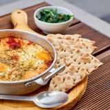 炒蛋用蕃茄、乳酪和香料在铝煎锅有把柄的有自创稀薄的lavash和水多的绿色的 免版税库存图片