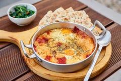 炒蛋用蕃茄、乳酪和香料在铝煎锅有把柄的有自创稀薄的lavash和水多的绿色的 库存照片