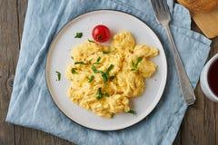 炒蛋,煎蛋卷,顶视图,关闭 早餐用pan-fried鸡蛋,茶,在老木桌上的蕃茄 免版税库存照片