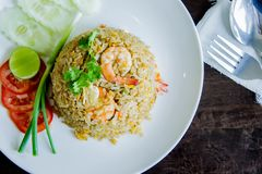 炒饭用在一个白色盘的虾在泰国foo的木桌上 图库摄影