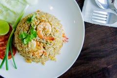 炒饭用在一个白色盘的虾在泰国foo的木桌上 免版税库存图片