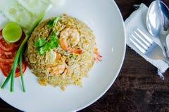 炒饭用在一个白色盘的虾在泰国foo的木桌上 免版税库存照片