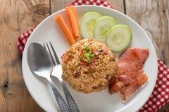炒饭用烟肉和菜在木桌上 免版税库存图片