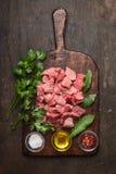 炖煮的食物的未加工的成份 猪肉立方体、油、盐和新调味料在老土气切板在黑暗的木背景冠上 免版税库存图片
