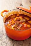 炖牛肉用土豆和红萝卜在红色砂锅 免版税库存图片