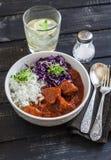 炖牛肉用米和红叶卷心菜在一个白色碗在黑暗的木背景 图库摄影