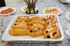 炖重汁肉丁-家庭东方酥皮点心用鸡蛋、橄榄和辣椒的果实和沙拉在桌上与桌布 免版税图库摄影