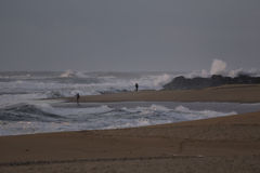 炫耀一个海滩的渔夫在一个风雨如磐的下午 免版税库存照片