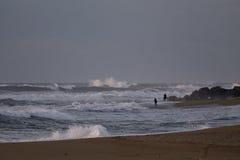 炫耀一个海滩的渔夫在一个风雨如磐的下午 免版税图库摄影
