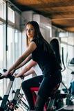 炫耀一辆固定式自行车的少妇在健身房 免版税库存图片