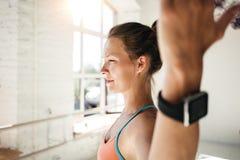 炫耀佩带巧妙的手表的妇女做健身锻炼 免版税库存照片