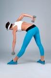 炫耀做倾斜的健身妇女对与哑铃的脚 免版税库存图片