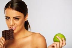 炫耀做出在健康苹果之间的妇女选择 免版税库存照片