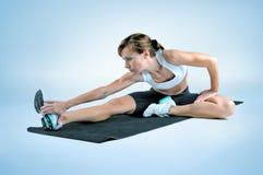 炫耀做在一张黑健身房席子的健身妇女锻炼 免版税库存图片
