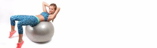 炫耀做在健身球的少妇锻炼 免版税库存图片