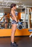 炫耀健身房的妇女。 免版税库存照片