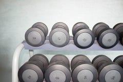 炫耀在现代体育俱乐部的哑铃 重量在健身房的训练器材 免版税库存照片