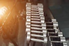 炫耀在现代体育俱乐部的哑铃 重量训练器材 免版税库存图片