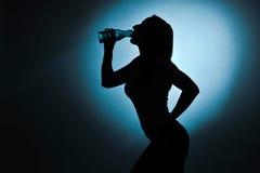 炫耀女孩饮用水,剪影演播室射击 免版税库存图片