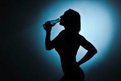 炫耀女孩饮用水,剪影演播室射击 库存图片