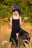 炫耀巫婆服装实践的瑜伽的女性 库存图片